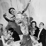 Frau tanzt auf dem Tisch bei einer Silvesterfeier
