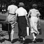 Rückenansicht von vier Frauen und einem Mann mit Koffern in der Hand